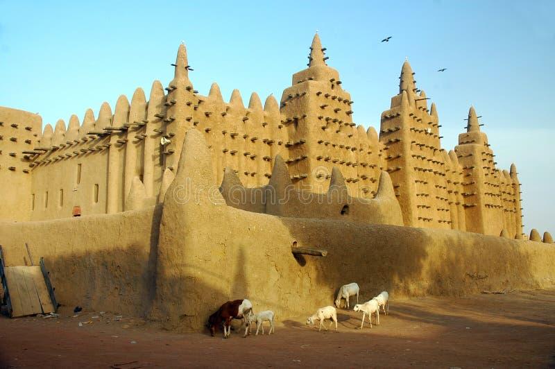 Animaux devant la mosquée de boue de Djenne images libres de droits