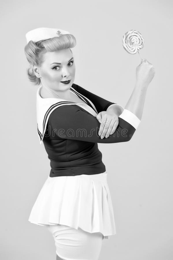 Anime blonde girl with lollipop in hand up. we can do lollipop! Sailor styled girl with candy in hand. Styled blonde with lollipop royalty free stock images