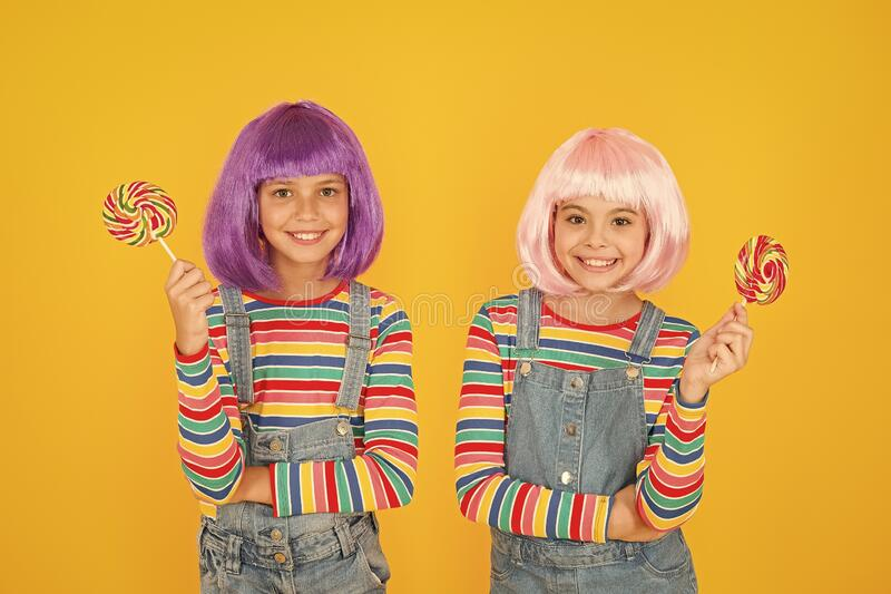 Anime cosplay party concept. Happy little girls. Anime fan. Kids with artificial hairstyles eating lollipops. Anime. Convention. Vibrant characters fantastical royalty free stock images
