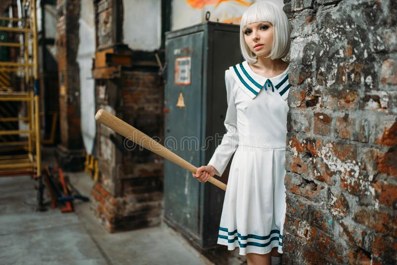 Anime girl with baseball bat in abandoned factory. Anime girl with baseball bat. Cosplay fashion, asian culture, doll in uniform, cute woman with makeup in stock photo