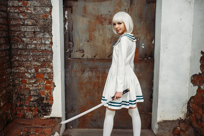Anime girl with sword poses on abandoned factory. Pretty anime style blonde girl with sword poses on abandoned factory. Cosplay fashion, asian culture, doll with stock images