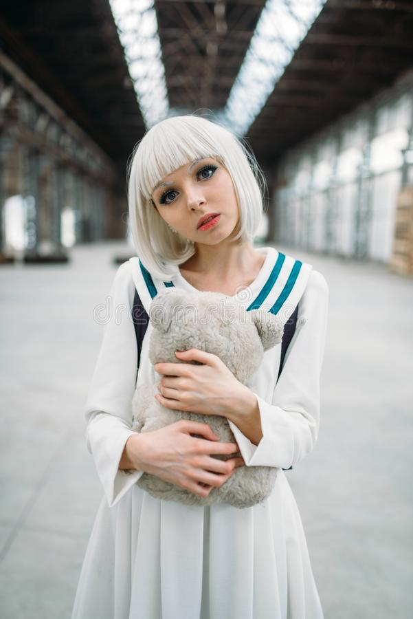 Anime style blonde girl hugs teddy bear. Cosplay woman, japanese culture, doll with toy on abandoned factory stock images