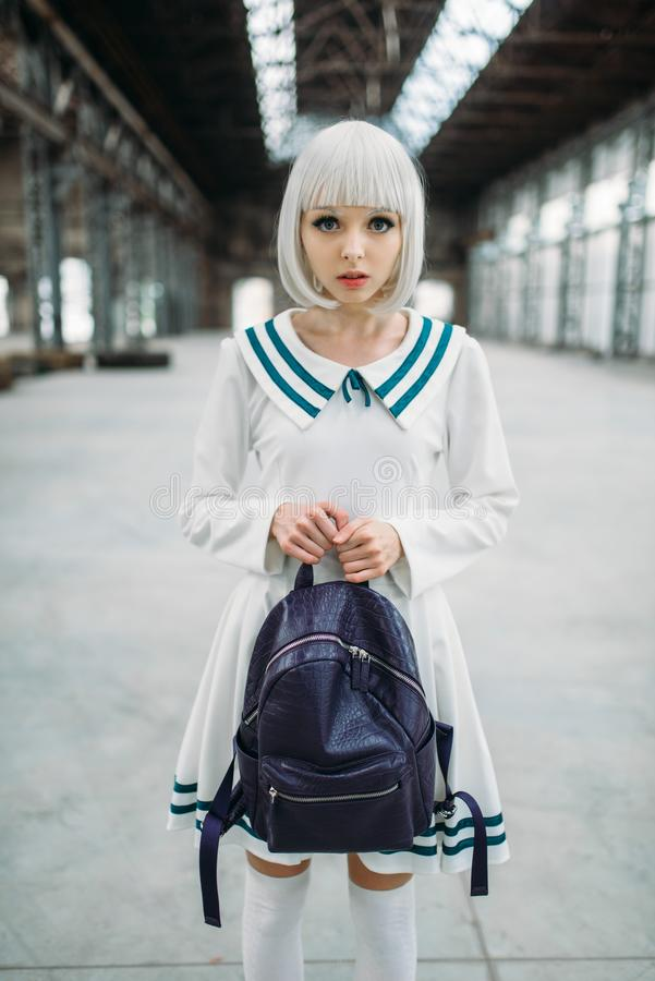 Anime style blonde girl hugs teddy bear. Cosplay woman, japanese culture, doll with toy on abandoned factory royalty free stock photography