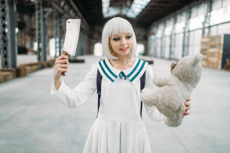 Anime style blonde girl with knife and teddy bear. Cute anime style blonde girl with knife and teddy bear in hands. Cosplay woman, japanese culture, doll with stock image