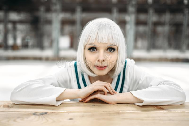 Anime style blonde lady with cold face. Cosplay fashion, japanese culture, glamour doll in dress, cute woman with makeup in the factory shop stock photos