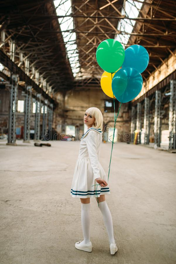 Anime style blonde lady with colorful air balloons. Pretty anime style blonde lady with colorful air balloons. Cosplay fashion, asian culture, doll in dress royalty free stock photo