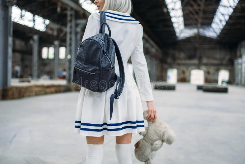 Anime style blonde woman looks at the toy bear. Cosplay girl, japanese culture, doll in dress on abandoned factory royalty free stock image