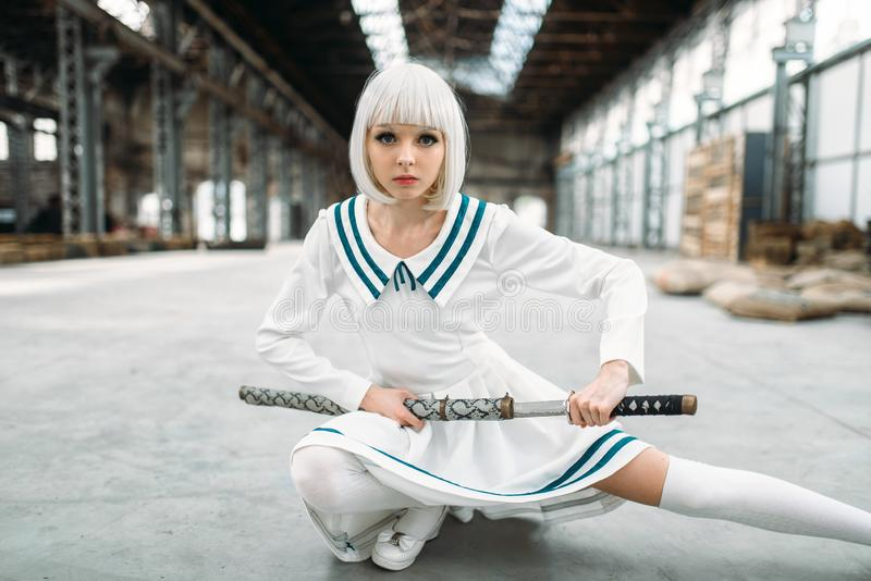 Anime style blonde woman with sword. Cosplay fashion, japanese culture, doll with blade on abandoned factory stock photos