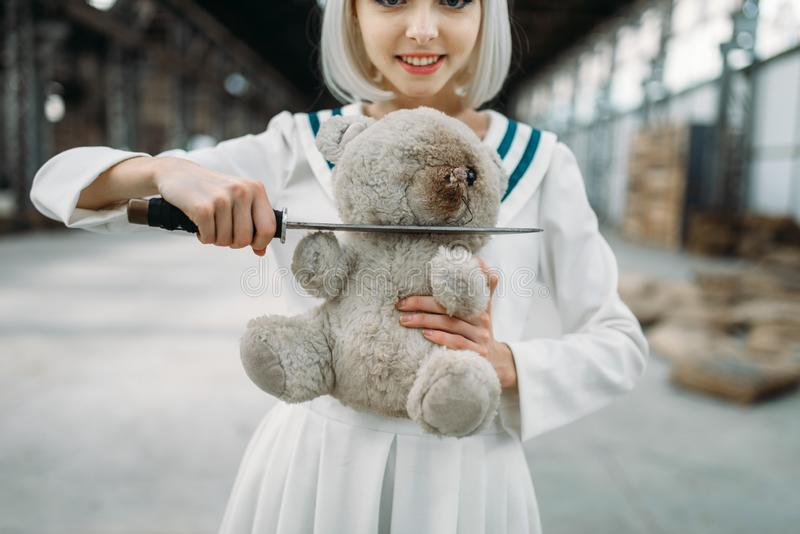 Anime style girl cuts off the head of a teddy bear. Anime style blonde girl with glass face cuts off the head of a teddy bear. Cosplay fashion, asian culture stock image