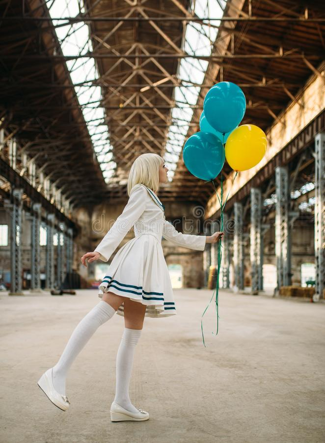 Anime style girl poses with colorful air balloons. Pretty anime style blonde girl poses with colorful air balloons. Cosplay fashion, asian culture, doll in dress stock images
