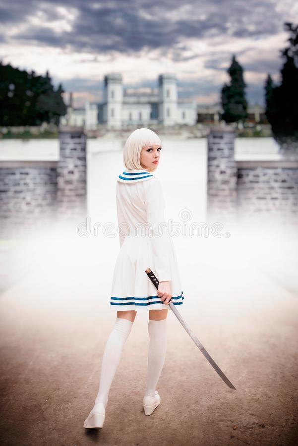 Anime style girl with sword against ancient castle. Anime style blonde girl with sword against ancient castle, back view. Cosplay woman, asian culture, doll with stock photo