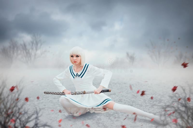 Anime style girl with sword in a snowy field. Anime style blonde girl with sword in a snowy field. Cosplay woman, japanese culture, doll with blade in cold tones stock photo