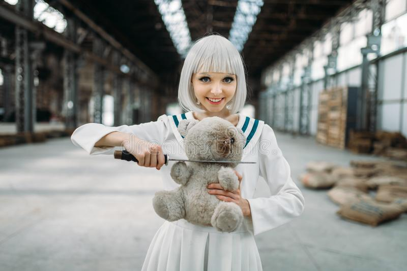 Anime style lady cuts off the head of a teddy bear. Anime style blonde lady with glass eyes cuts off the head of a teddy bear. Cosplay fashion, asian culture stock image