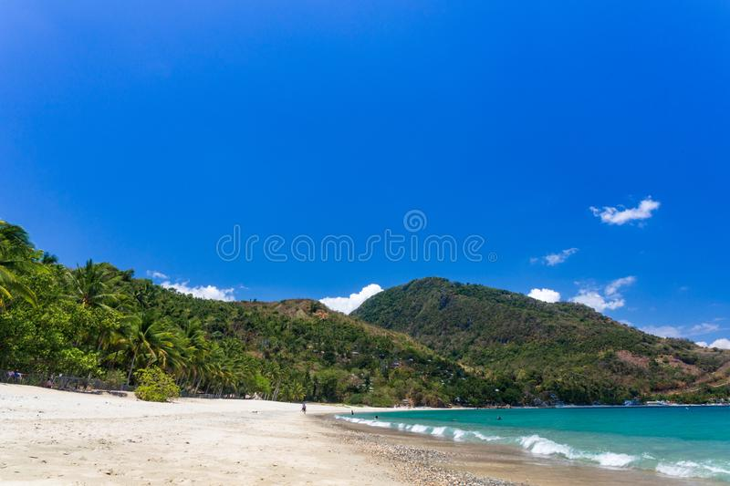 Aninuan beach, Puerto Galera, Oriental Mindoro in the Philippines, white sand, coconut trees and turquoise waters, landscape view. Aninuan beach in Puerto Galera royalty free stock photography