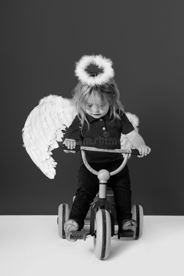 Anioł chłopiec na czerwonym tle na rowerze obraz royalty free