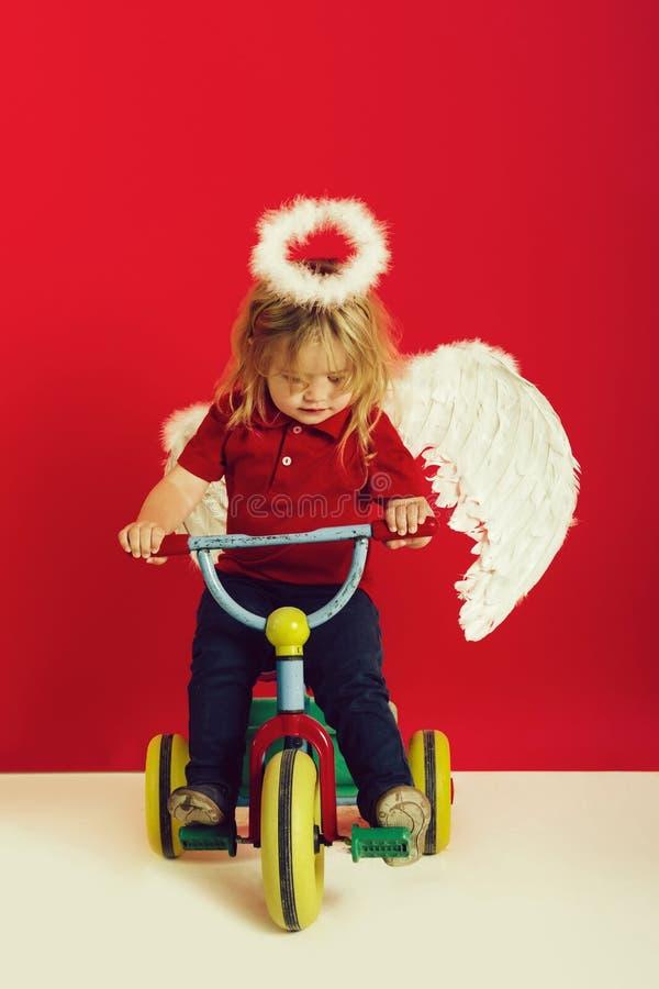 Anioł chłopiec na czerwonym tle na rowerze zdjęcie royalty free