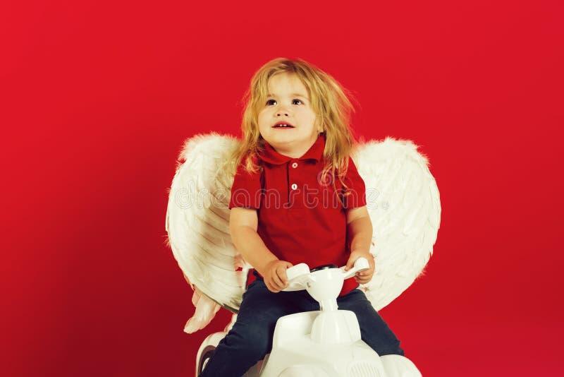 Anioł chłopiec na czerwonym tle na samochód zabawce obrazy royalty free