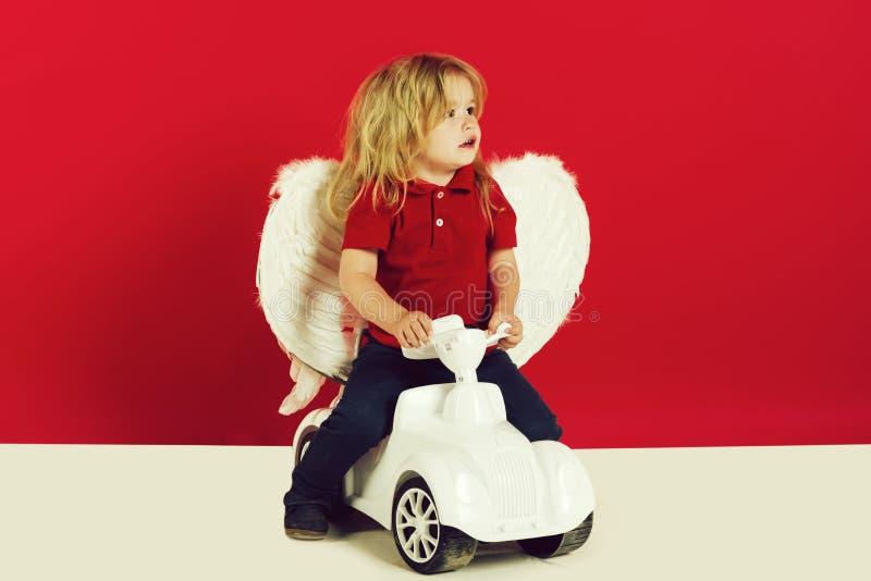 Anioł chłopiec na czerwonym tle na samochód zabawce zdjęcie royalty free
