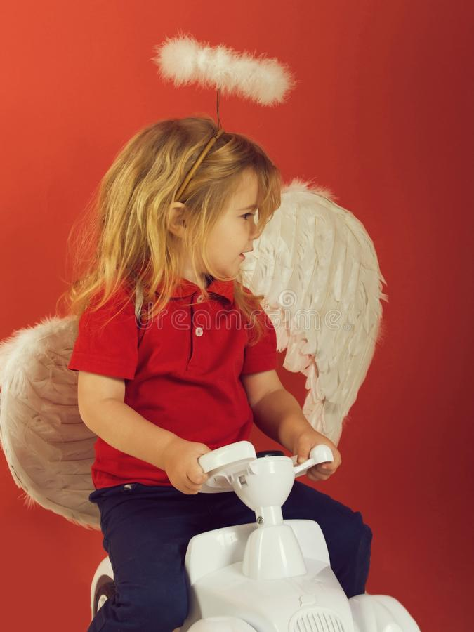 Anioł chłopiec na czerwonym tle na samochód zabawce zdjęcia royalty free