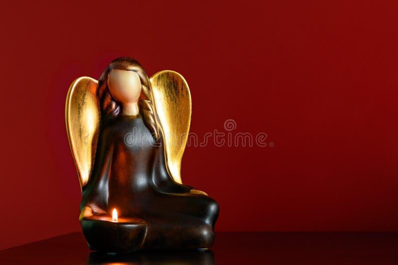 Anioł postaci candlestick na wezgłowie stole z płonącym candl fotografia stock