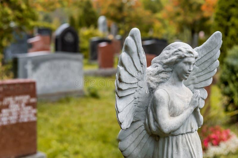 Anioł statuy modlenie przed kilka nagrobkami na graveya fotografia stock