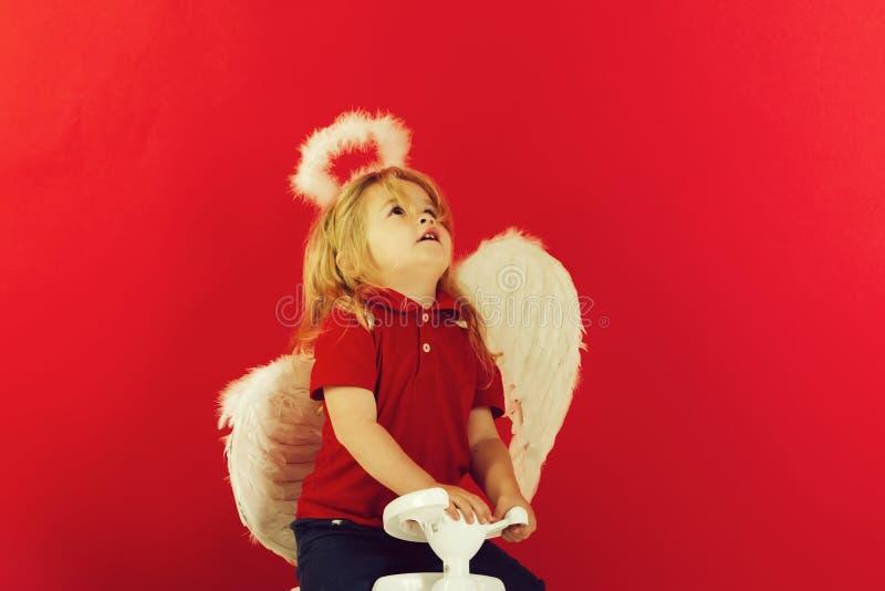 Anioł szczęśliwa chłopiec na czerwonym tle dla valentine powitania fotografia stock