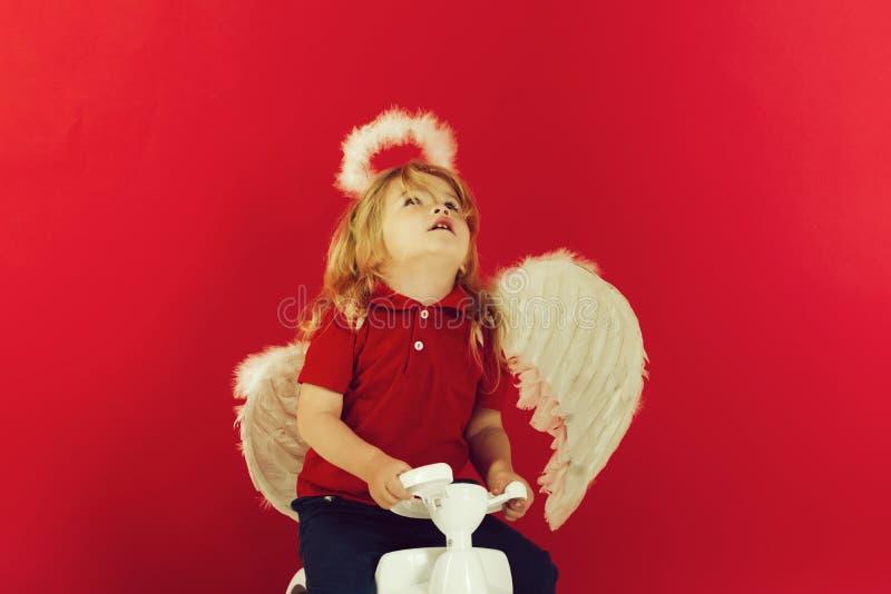 Anioł szczęśliwa chłopiec na czerwonym tle dla valentine powitania obraz stock