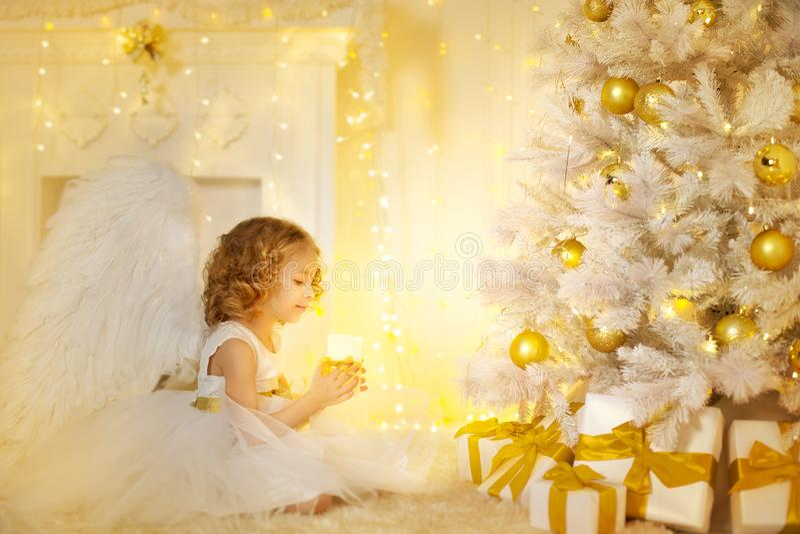 Anioła dziecko i choinka z teraźniejszość prezentami, dzieciak dziewczyna zdjęcia stock