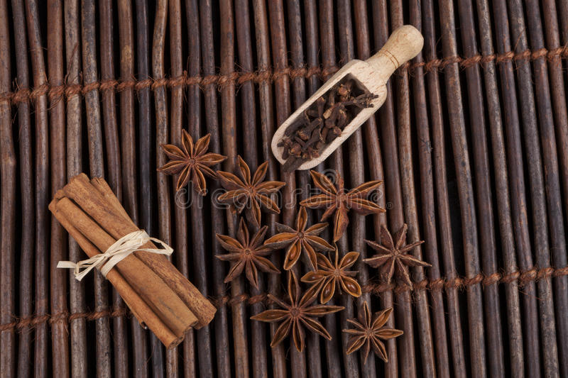 Anis on Dark Wood. Cinnamon sticks with star shape anis on dark wood background royalty free stock image