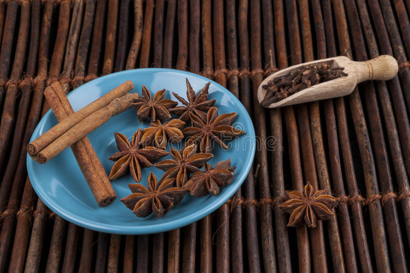 Anis Stars on Blue. Cinnamon sticks with star shape anis on blue plate and wood background royalty free stock images