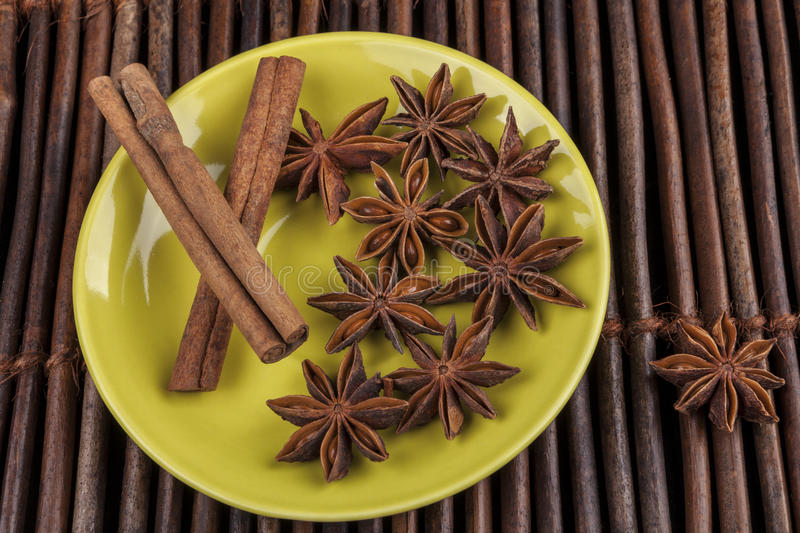 Anis Stars on Green. Cinnamon sticks with star shape anis on green plate and wood background stock photo