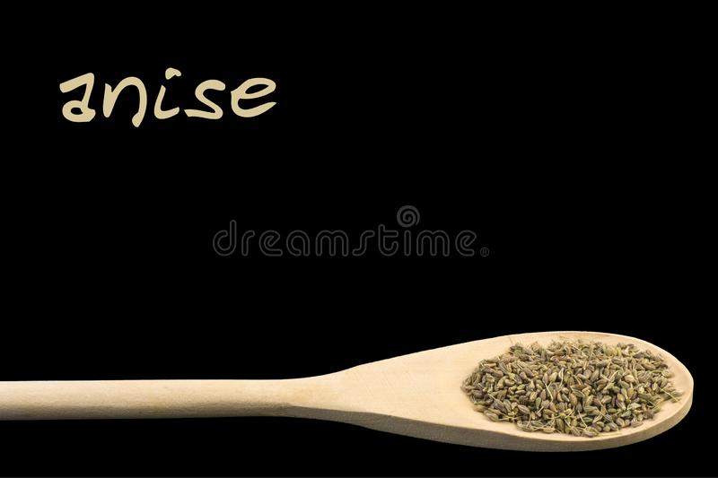 Anise on wooden spoon isolated on black background. Latin name Pimpinella stock image