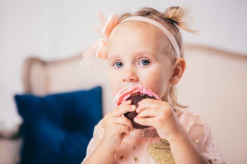 Aniversário do ` s das crianças a menina caucasiano com dois anos engraçada no vestido cor-de-rosa que está ao quarto da casa o f fotografia de stock royalty free