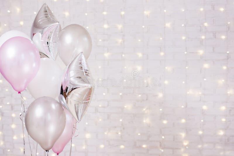 Aniversário e conceito do Natal - fim acima de balões de ar sobre o fundo da parede de tijolo com luzes fotografia de stock