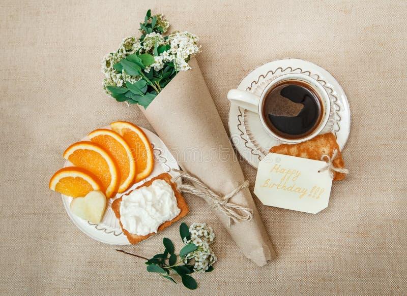Aniversário romântico BreakfastCup saudável do café, laranja do corte, biscoito com requeijão Cartão do desejo com flor imagens de stock royalty free