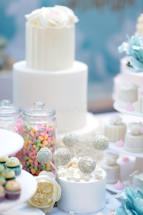Aniversario tradicional/casarse la torta de m?ltiples capas adornada con las flores Y postre dulce delicioso hermoso - magdalenas fotos de archivo