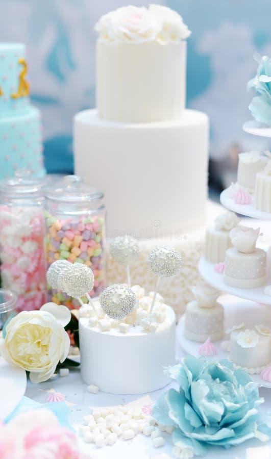 Aniversario tradicional/casarse la torta de m?ltiples capas adornada con las flores Y postre dulce delicioso hermoso - magdalenas foto de archivo libre de regalías