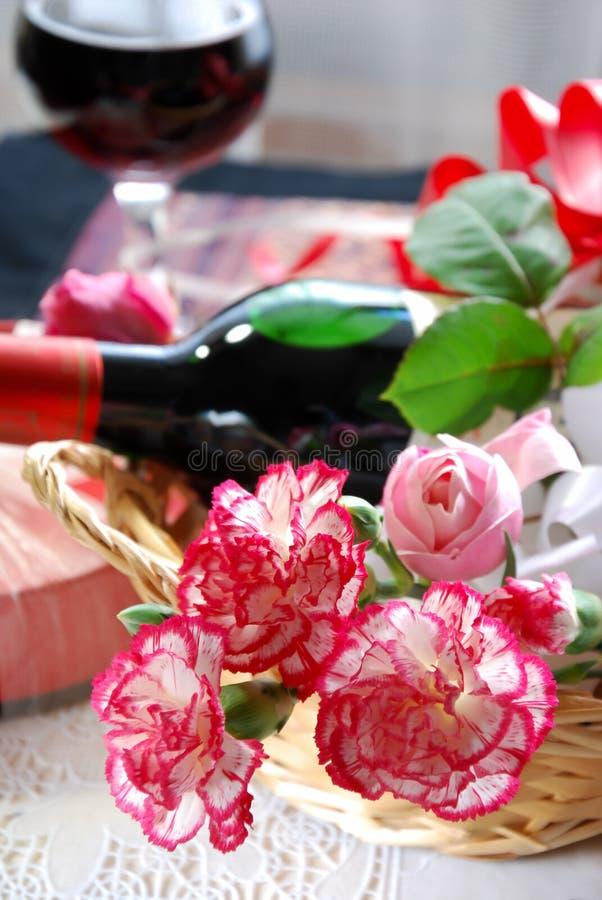 Anjerbloemen met rode wijn stock fotografie