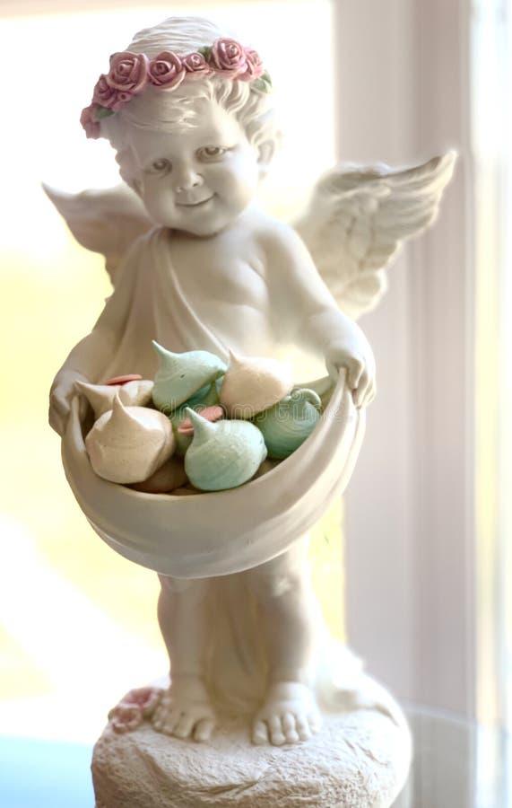 Anjo branco com uma grinalda da cor de rosas cor-de-rosa e das folhas verdes As merengues são turquesa e branco imagens de stock