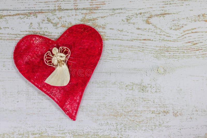 Anjo branco em um coração vermelho Dia feliz do ` s do Valentim do cartão Fundo de madeira claro, lugar para o texto, cartão do V imagem de stock royalty free