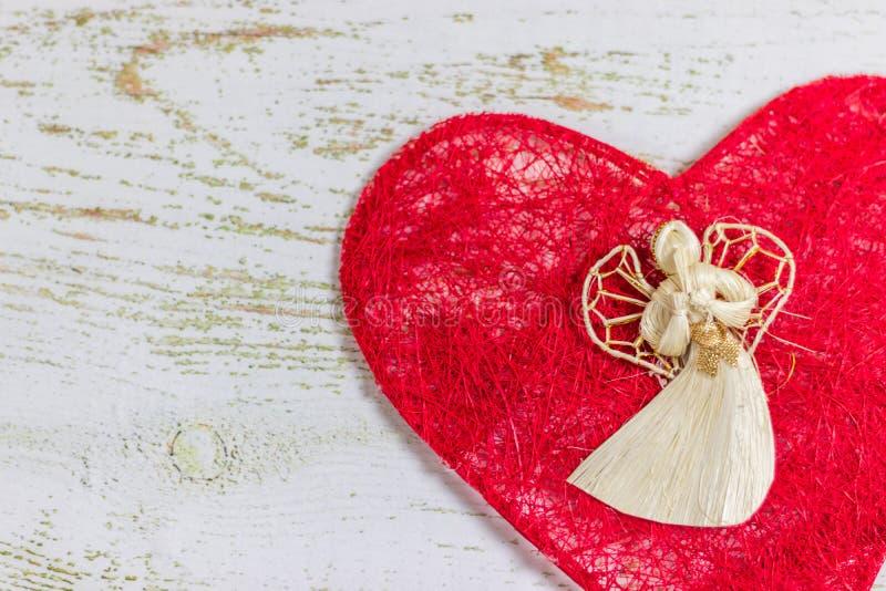 Anjo branco em um coração vermelho Dia feliz do ` s do Valentim do cartão Fundo de madeira claro, lugar para o texto, cartão do V fotografia de stock royalty free