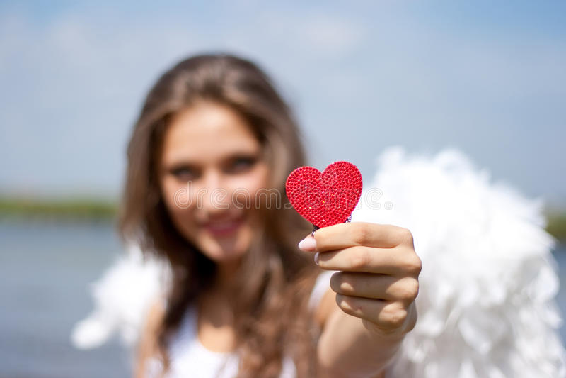 Anjo com coração vermelho ao ar livre fotografia de stock