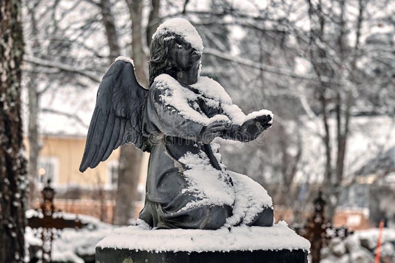 Anjo congelado coberto com a neve na jarda grave do cemitério no inverno imagens de stock royalty free