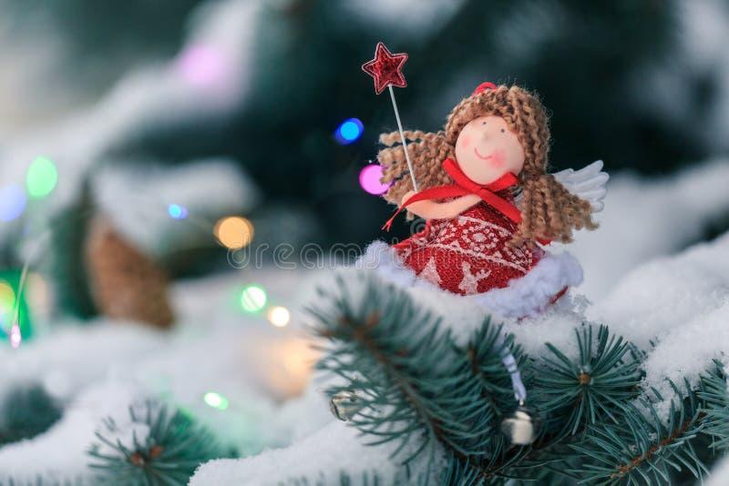 Anjo em um ramo do abeto na madeira coberto de neve Decoração do Natal fotografia de stock