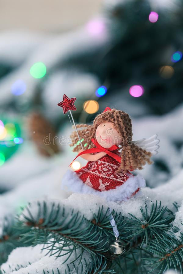 Anjo em um ramo do abeto na madeira coberto de neve Decoração do Natal imagens de stock royalty free