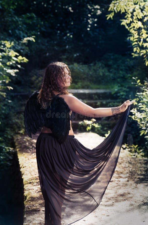 Anjo fêmea com asas pretas em um fundo preto foto de stock royalty free