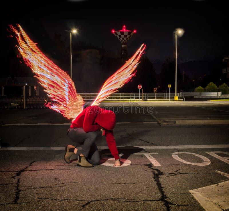 Anjo masculino caído com asas do fogo foto de stock