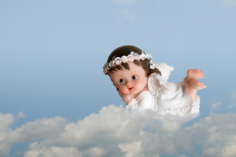 Anjo pequeno bonito nas nuvens no fundo do céu azul imagens de stock royalty free