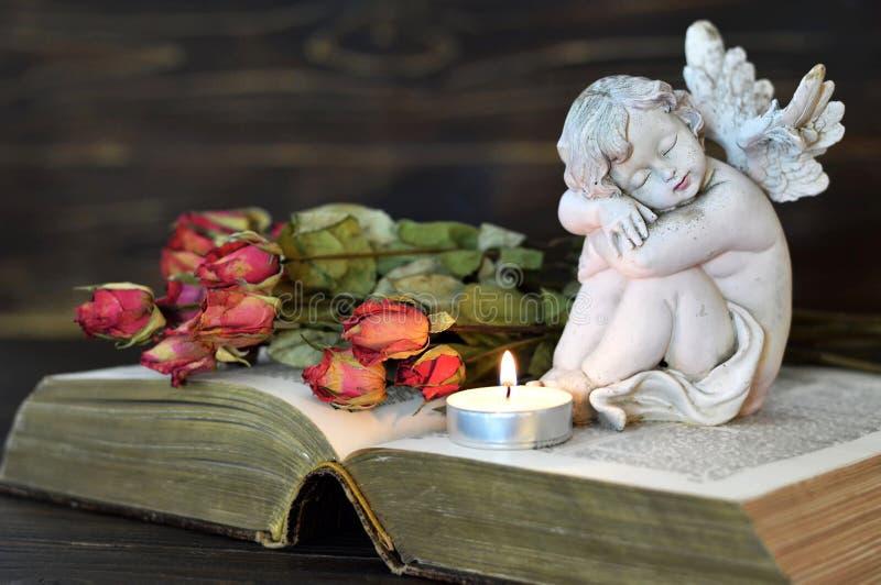 Anjo, vela e rosas secas foto de stock royalty free