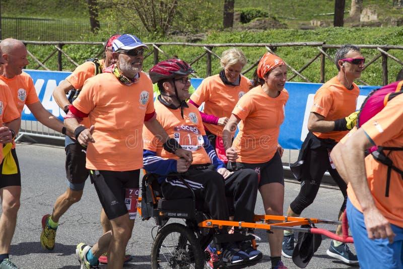Anjos de corrida que levam um homem na cadeira de rodas na raça de maratona de Roma de 2019 fotos de stock